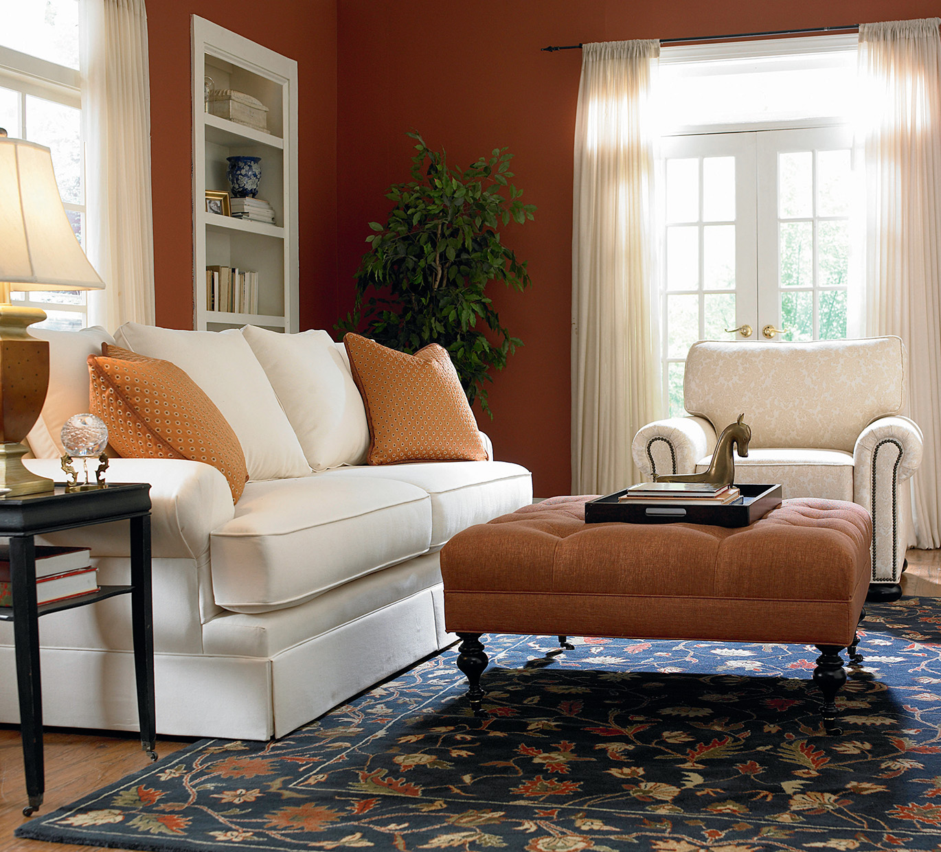 white sofa and chair with orange ottoman