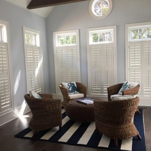 sitting area with shutters on windows and chairs