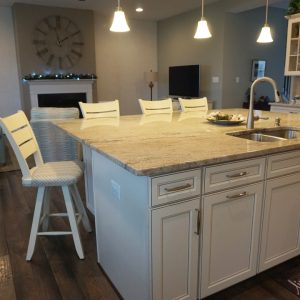 kitchen island with sink and chairs all around
