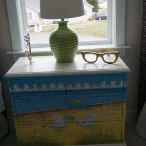 lamp and glasses on night stand next to window
