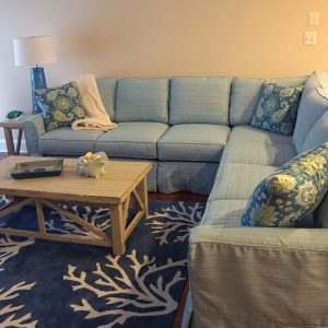 blue sectional with coffee table on blue carpet