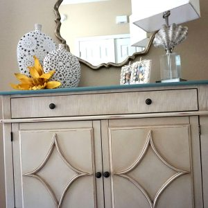 vases and lamp on cabinet under mirror
